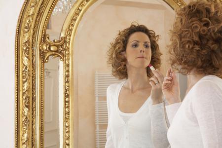 appearance: woman applying lipstick in mirror