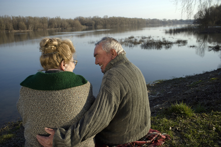 Senior couple sitting on rug by river, rear view, man smiling LANG_EVOIMAGES
