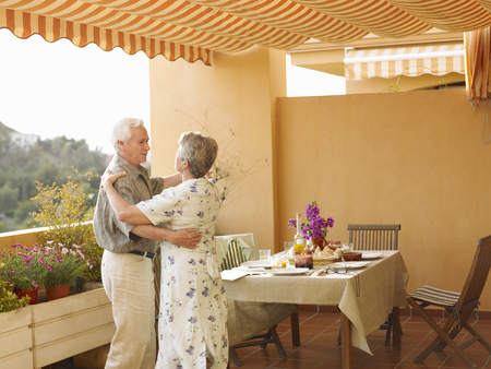 50 something: Senior couple dancing beside dining table on balcony LANG_EVOIMAGES