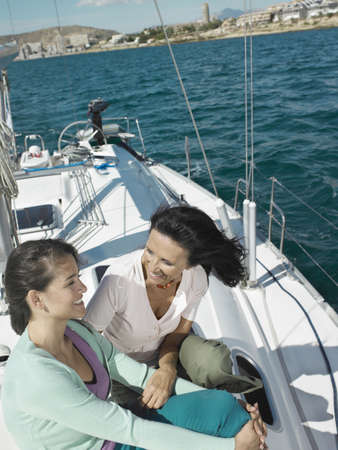 50 something: Mature mother and daughter relaxing on yacht, smiling LANG_EVOIMAGES