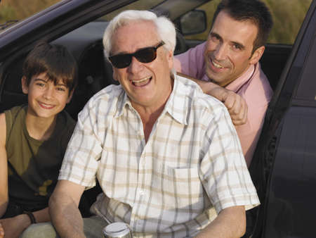 50 something: Boy (8-10) sitting with father and grandfather in parked car, smiling, portrait