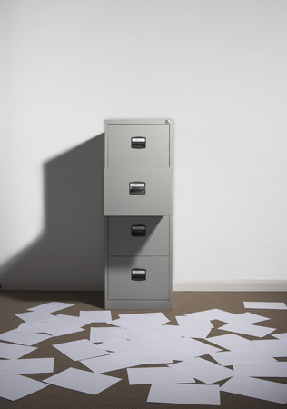 Filing cabinet against wall with papers strewn about.