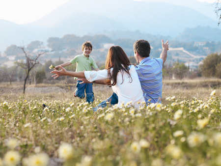 mamma: Parents sitting in field holding out arms to son (6-8), smiling LANG_EVOIMAGES