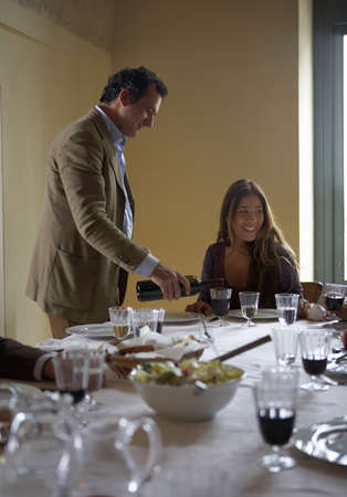 40 something: Man pouring wine for woman at dinner table LANG_EVOIMAGES