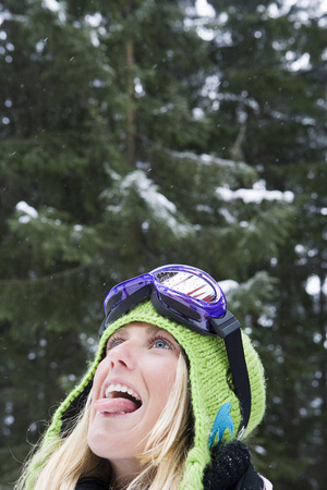 Close-up of young blonde woman wearing ski-wear sticking tongue out to catch snow LANG_EVOIMAGES