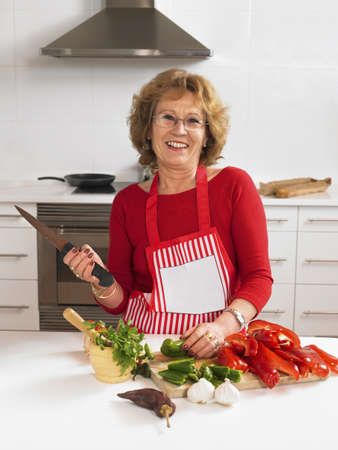 50 something: Mature woman chopping vegetables in kitchen, smiling, portrait