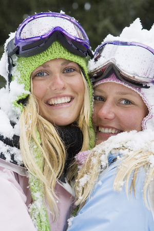 wintery: Close-up of two young blonde women in ski-wear embracing