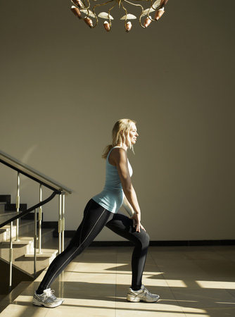 Woman stretching by steps, side view