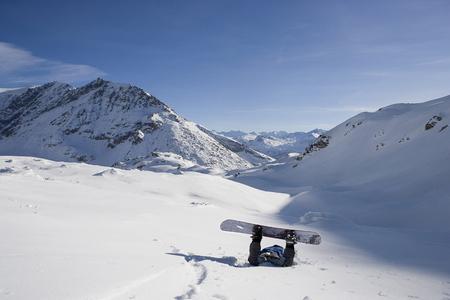 Fallen male snowboarder lying face down in snow