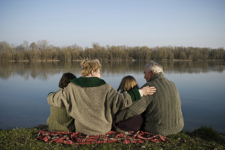 Grandparents, grandson (12-14) and granddaughter (10-12) sitting by river, rear view