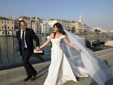 thirtysomething: Bride and groom walking. Grand Canal, Venice, Italy. LANG_EVOIMAGES