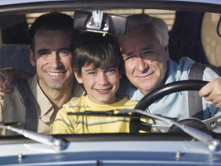 other side: Boy (8-10) sitting in car with father and grandfather, smiling, portrait LANG_EVOIMAGES