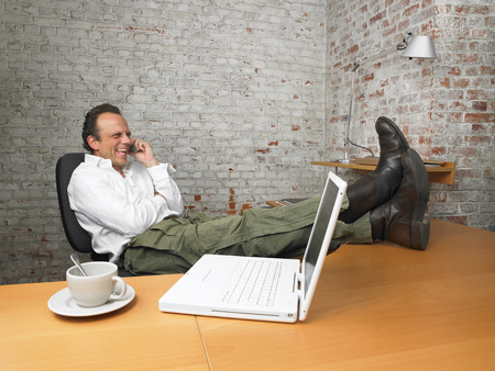 successfulness: Businessman laughing on the phone, feet on desk. ,Brussels, Belgium. LANG_EVOIMAGES