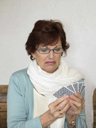 disillusioned: Senior woman playing cards, pulling face
