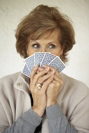 passtime: Senior woman holding playing cards over face, close-up LANG_EVOIMAGES