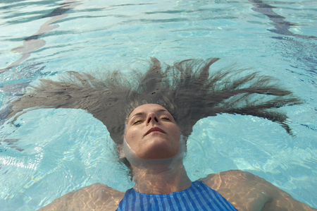passtime: Woman with long hair floating in swimming pool, eyes closed