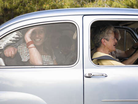 thirtysomething: Multi-generational family sitting in car, side view, smiling