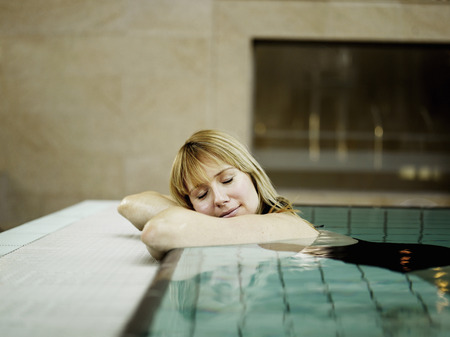 Woman relaxing by poolside, eyes closed LANG_EVOIMAGES
