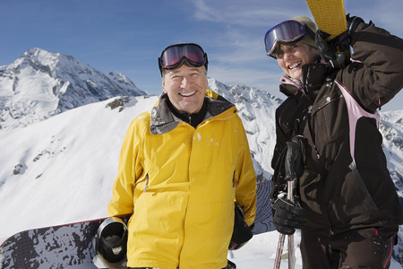 Mature couple in ski-wear holding Skis and snowboard on mountain
