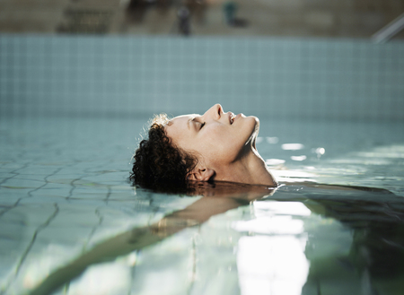 captivated: Woman lying in water, side view LANG_EVOIMAGES