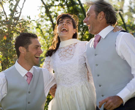50 something: Young bride and groom and mature father jumping, smiling
