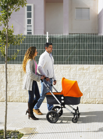 Couple walking with pram on pavement, Alicante, Spain, LANG_EVOIMAGES