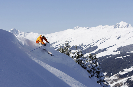 Austria, Saalbach, man skiing down slope, mountains in distance