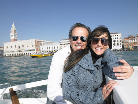 Italy, Venice, couple wearing sunglasses on boat, smiling