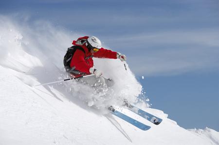 Austria, Saalbach, man skiing on slope sending up snow spray LANG_EVOIMAGES