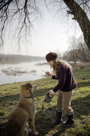 Girl (10-12) standing by river holding piece of cake in front of dog LANG_EVOIMAGES