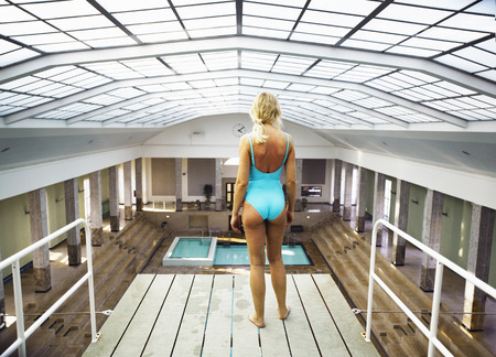 Mature woman standing on diving board, rear view