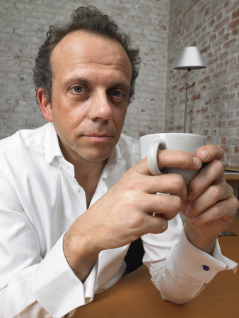 captivated: Pensive businessman looking at camera holding coffee cup. ,Brussels, Belgium.