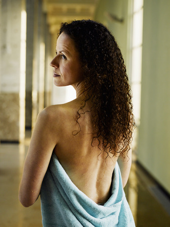 Woman wrapped in towel, rear view