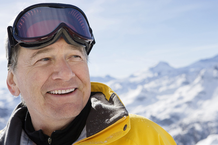 Mature male in ski-wear on mountain, close-up, portrait