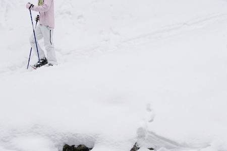 low section: Low section side view of young woman walking in snow-shoes LANG_EVOIMAGES