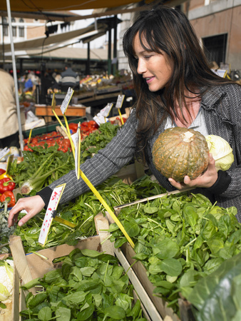 Woman choosing vegetables at Rialto market. Venice, Italy.