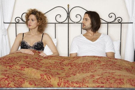 young couple in bed wearing underwear, woman looking away from man