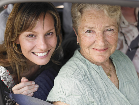Senior woman and adult daughter sitting in car, smiling, portrait LANG_EVOIMAGES