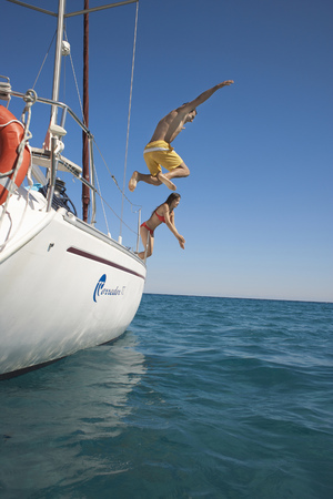Young couple jumping off yacht into sea