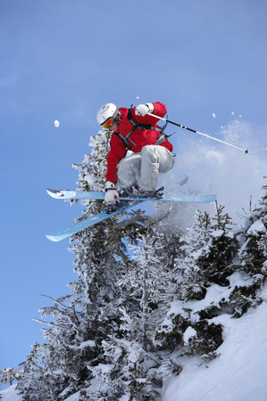 Austria, Saalbach, male skier jumping through trees with skis crossed