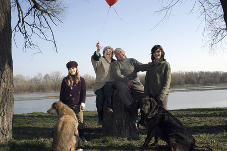 Grandparents, grandson (12-14) and granddaughter (10-12) with two dogs by river