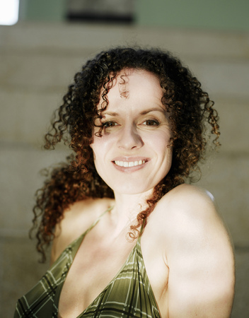 Woman sitting by swimming pool, smiling, portrait
