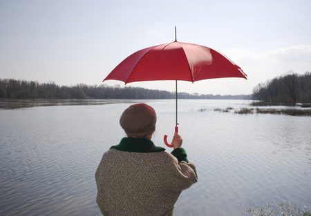 freeing: Senior woman standing by river holding red umbrella, rear view LANG_EVOIMAGES