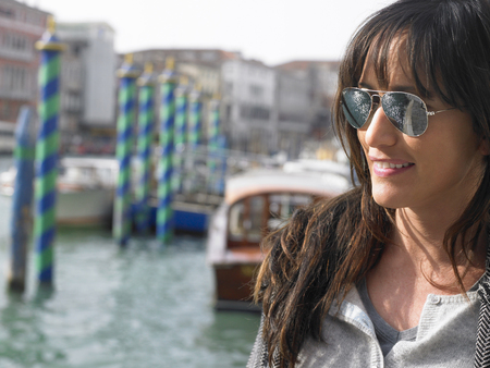 Portrait of woman wearing sunglasses. Rialto, Venice, Italy.