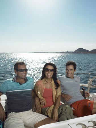 Young man and mature couple relaxing on yacht, smiling LANG_EVOIMAGES