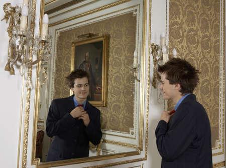 appearance: Teenage boy (15-17) wearing suit looking in mirror