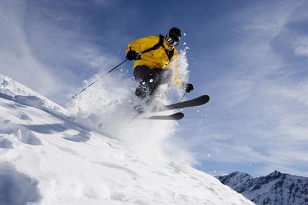 Male skiing over mountain ridge