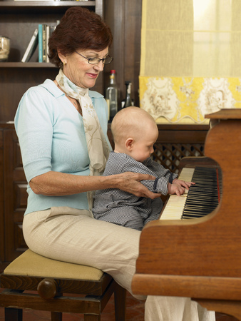 Senior grandmother playing piano with baby grandson (1-3 months)