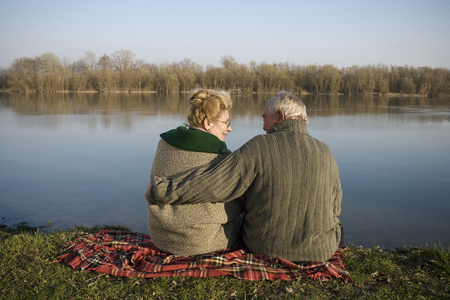Senior couple sitting on rug by river, rear view, woman smiling LANG_EVOIMAGES