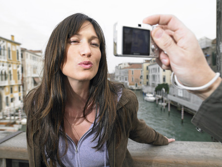 Italy, Venice, woman blowing kiss to camera held by man